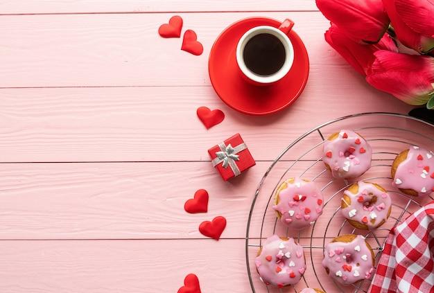 ピンクの木製の背景で隔離のコーヒーとドーナツとバレンタインデーのbrackfast