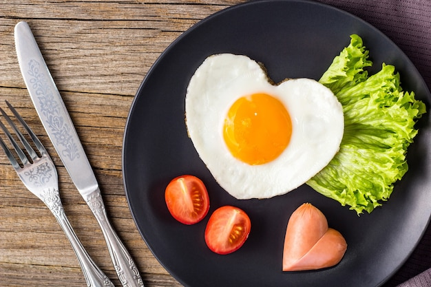 Valentines day breakfast with heart shaped fried eggs served on grey plate