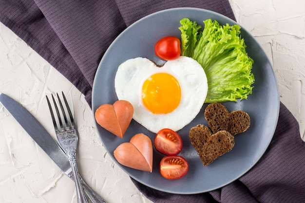 Завтрак в день святого валентина с яичницей в форме сердца, подаваемой на серой тарелке. плоская планировка, вид сверху