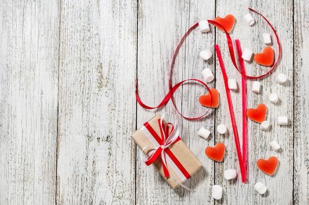 バレンタインデーのキャンディーハートマシュマロと白い木製の背景の上にクラフト紙のギフトの箱。