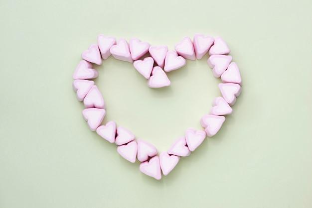 緑の背景にバレンタインデーのキャンディーハートマシュマロ