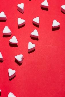 赤い背景の上のバレンタインデーのキャンディーハートマシュマロ