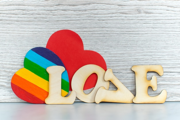 Valentines day card background, rainbow cute heart like a lgbt pride rainbow flag with red paper heart and decorative wooden word. valentine day romantic. love human rights and freedom concept.