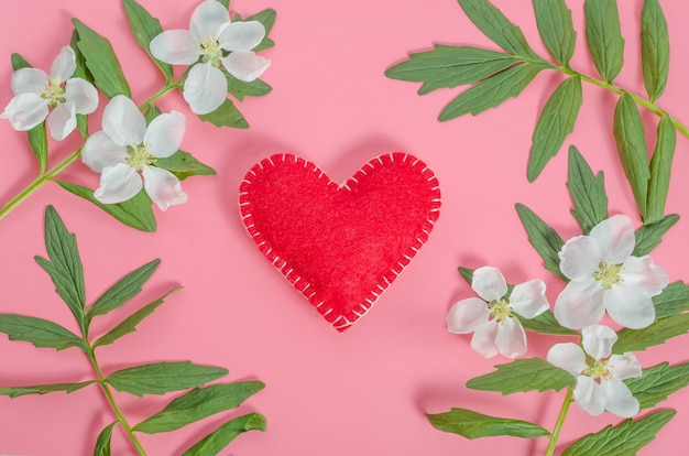 Valentines day card, red heart with a frame of flowers and leaves on a pink background