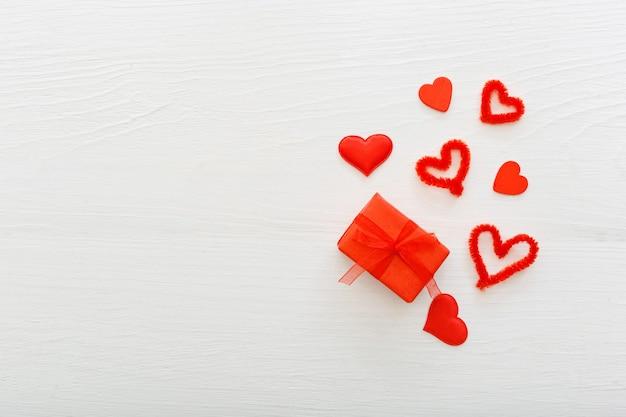 コピースペースフレーム付きバレンタインデーカード。ハートと白い木製の背景プレゼントギフトテープ。バレンタインデーの愛のロマンスハートの概念。バレンタインデーの構成、パターン。上面図、フラットレイ。