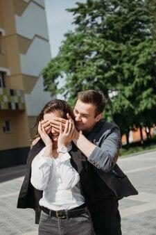 Празднование дня святого валентина, любовь и знакомство на открытом воздухе. счастливая любящая пара, прогулки по улице города. угадайте кто, молодой человек удивил свою девушку, положив руки ей на глаза.