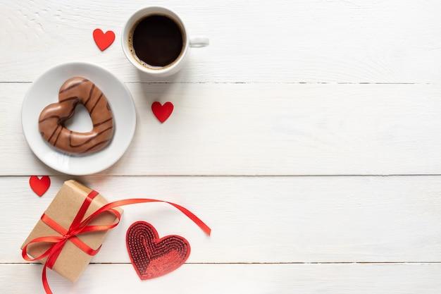 День святого валентина. кофе, шоколадное печенье в форме сердца, подарочная коробка и бумажная карточка с ремесленным конвертом на белом деревянном столе. плоский стиль.