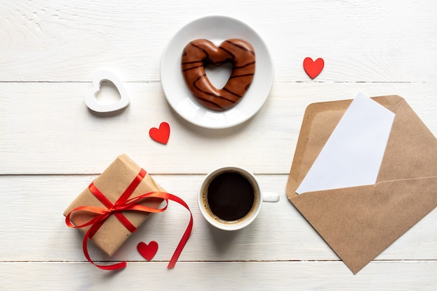 Valentines day. coffee, heart shaped chocolate cookie, gift box and paper card with craft envelope on white wooden table top view. flat lay style.