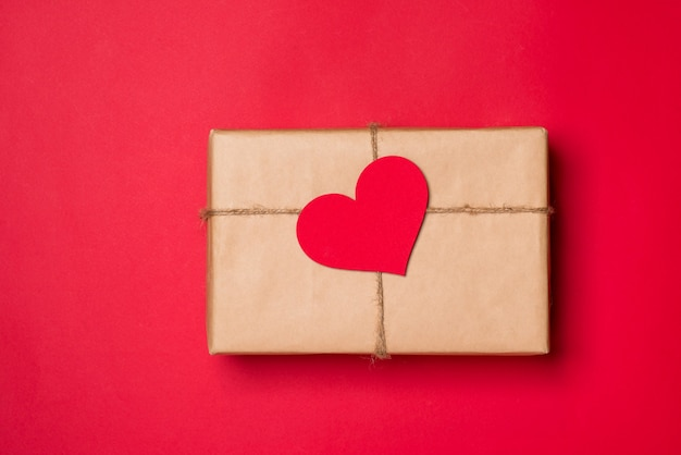 발렌타인 데이 구성: 빨간색 배경에 활과 하트가 있는 선물 상자.