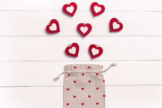 День святого валентина композиция. сердца, ecobag на белой деревянной поверхности. плоская планировка, вид сверху, сверху, копия пространства