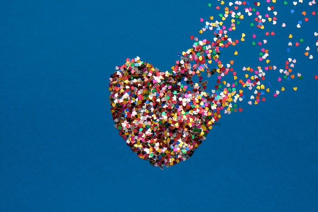 Valentines day composition with broken heart made from confetti on classic blue background