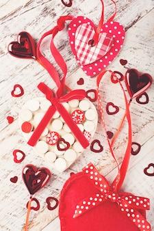 Состав дня святого валентина с сердечками на винтажной деревянной поверхности. тонированное фото