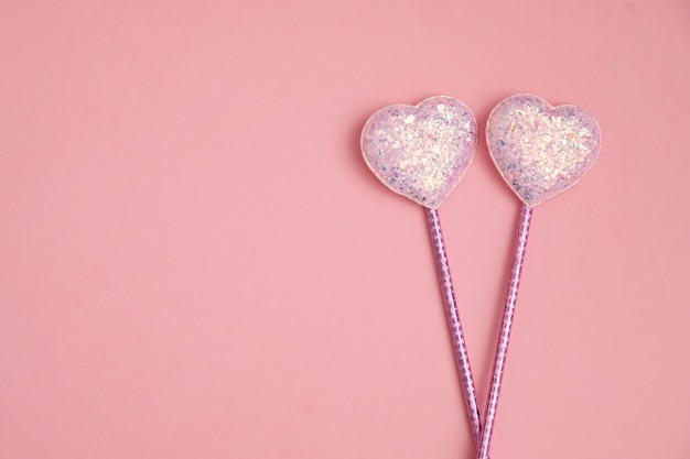 Valentines day composition with two glitter hearts on pink background, flat lay