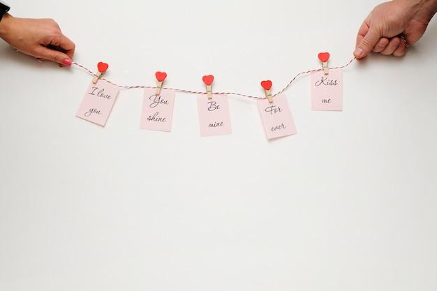 Состав дня валентинок: женщина и человек держа зрелый с сообщениями влюбленности на белой предпосылке. пространство для текста.