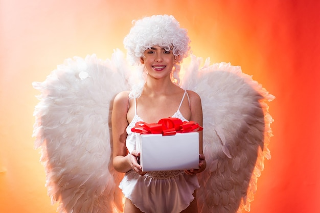 Valentines day concept. angel with gift. art photo of a angelic beautiful woman. angel woman with feather white wings and gift. love concept