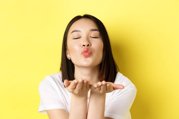 발렌타인 데이 개념. 닫기 아름 다운 아시아 여자 주름 입술과 입 근처 손을 잡고, 닫힌 된 눈으로 카메라에 공기 키스를 날려, 노란색 위에 서.