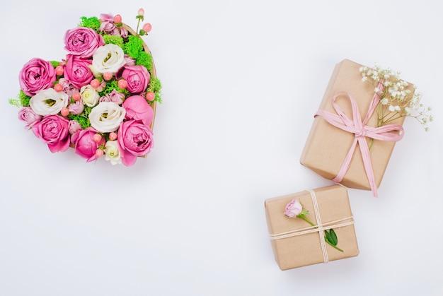 Концепция дня святого валентина. крафт-бумага упаковывая подарочные коробки и цветочную коробку в форме сердца на белом фоне с пустым пространством для текста. вид сверху, плоская планировка.