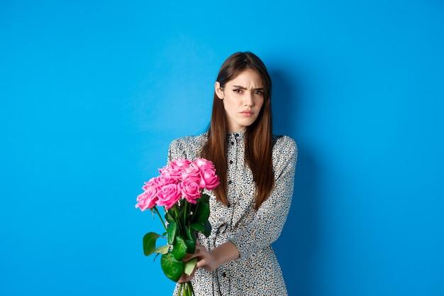 Il giorno di san valentino concetto dispiaciuto giovane donna che rifiuta il regalo di fiori accigliata e smorfie rifiutando...
