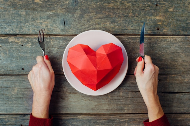 Valentines day concept female hands ready to eat paper volume heart on the plate on rustic wooden background. top view, flat lay.