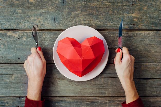 バレンタインデーのコンセプト素朴な木製の背景のプレートに紙のボリュームの心を食べる準備ができて女性の手。上面図、フラットレイ。