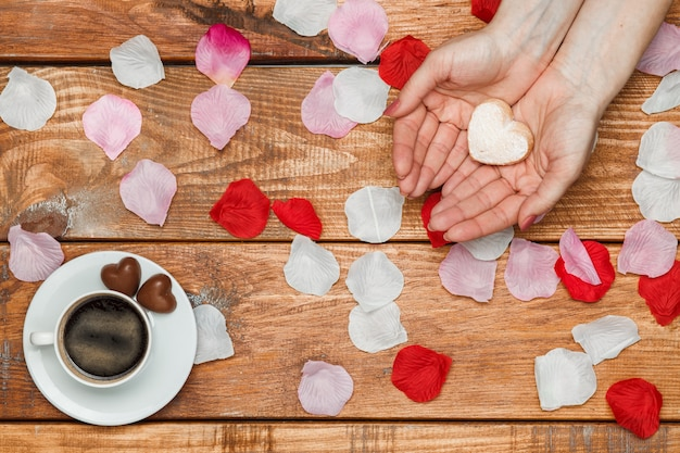 Valentines day concept. female hands with hearts on wooden with flower petals and cup of coffee