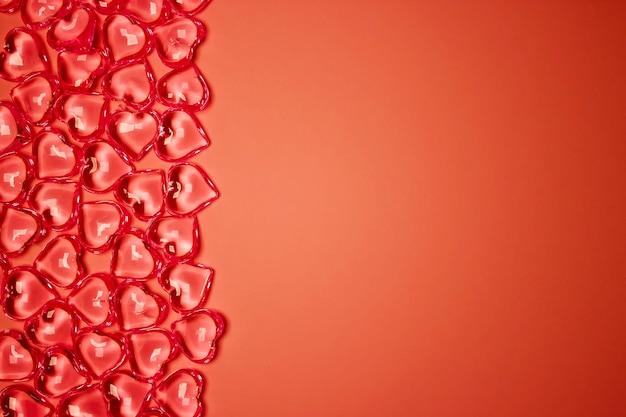 バレンタインデーのコンセプト。ピンクの背景にガラスの透明なハート、ガラスのハートの輝き、ガラスの絵。多くの赤いガラスの心。バレンタインデーが大好きです。テキスト用のスペースを空にします。