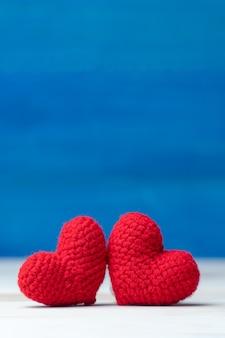 День святого валентина концепция рука делает две пряжи красное сердце на деревянном столе