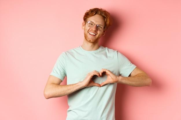 발렌타인 데이 개념. 잘 생긴 빨간 머리 남자 안경에 심장 기호를 표시 하 고 분홍색 배경 위에 서있는 당신을 사랑합니다.
