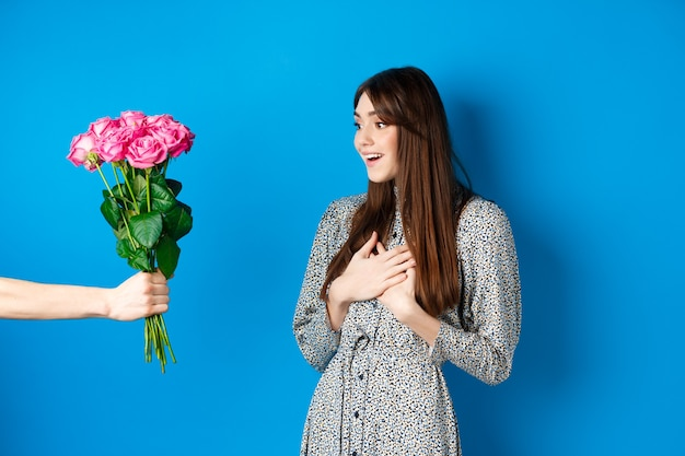 Immagine del concetto di san valentino di bella ragazza sorpresa che guarda a portata di mano con un mazzo di fiori rec...