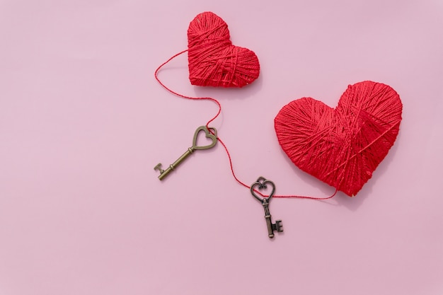Valentines day concept, key and red hearts isolated on pink background.