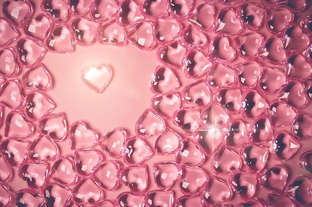 バレンタインデーのコンセプト。ピンクの背景にガラスの透明なハート、ガラスのハートが光る、ガラスの絵。多くの赤いガラスの心。バレンタインデーが大好きです。スペースをコピーします。