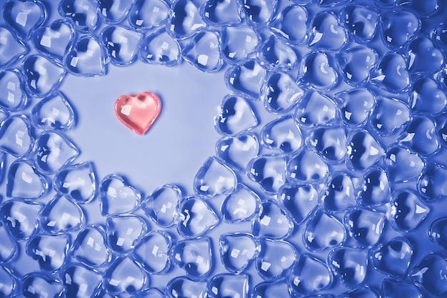 バレンタインデーのコンセプト。ピンクの背景にガラスの透明なハート、ガラスのハートが光る、ガラスの絵。トレンドカラークラシックブルー。 2020年の色。コピースペース。