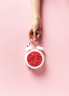 Valentines day concept pastel minimalis, time to gift, alarm clock and hand