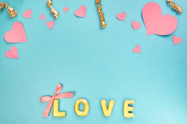 バレンタインデーのコンセプトピンクの紙の心の紙吹雪と青い背景の上の言葉の愛上面図
