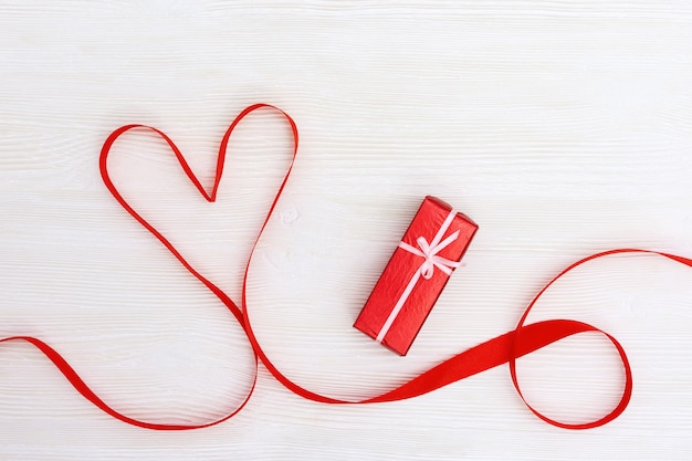 Valentines day concept. red heart from ribbon and surprise box on white wooden