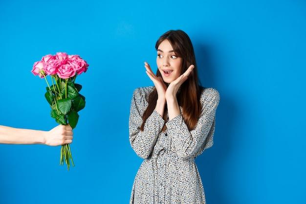バレンタインデーのコンセプト。花で手に驚いて見えるロマンチックな女の子、ピンクのバラの花束を受け取る女性、青い背景の上に立って