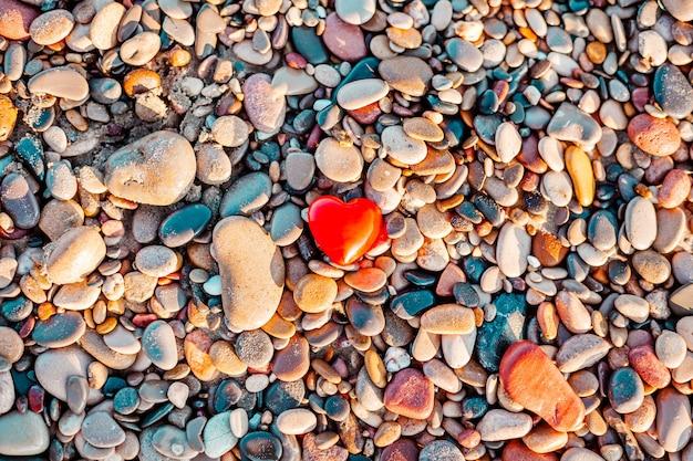 バレンタインデーのコンセプト。コピースペースのある小石のビーチに赤いハートのロマンチックな愛のシンボル。
