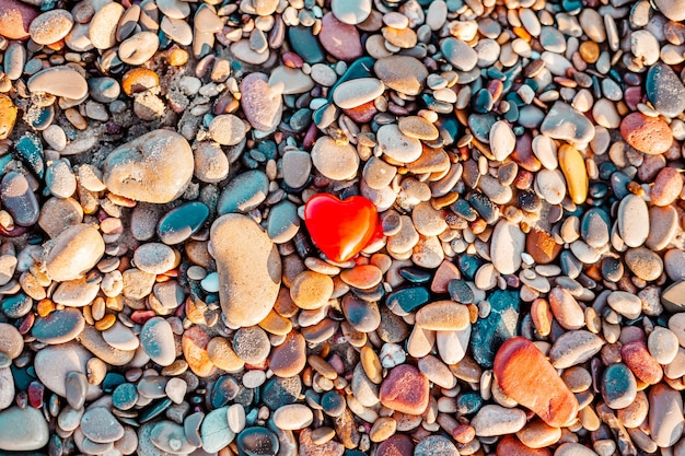 Valentines day concept. romantic love symbol of red heart on the pebble beach with copy space.