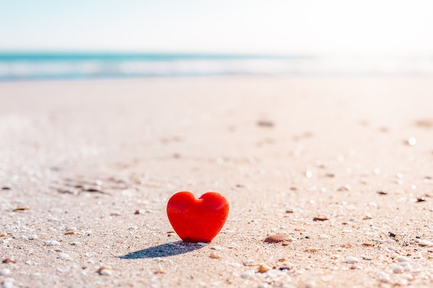 Valentines day concept. romantic love symbol of red heart on the sand beach with copy space.