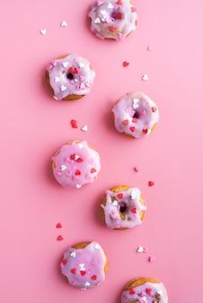 バレンタインデーのコンセプト。ピンクの背景に分離された小さなドーナツ