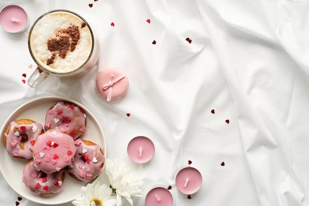 バレンタインデーのコンセプト。コーヒーのカップと白いベッドの上の小さなドーナツ