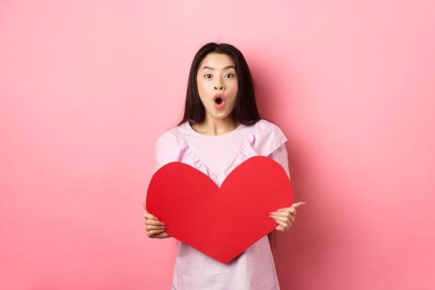 Концепция дня святого валентина. удивленная азиатская девочка-подросток говорит «вау», показывая большую красную сердечную открытку, получает подарок от тайного поклонника или любовника, стоя в романтическом платье на розовом фоне.