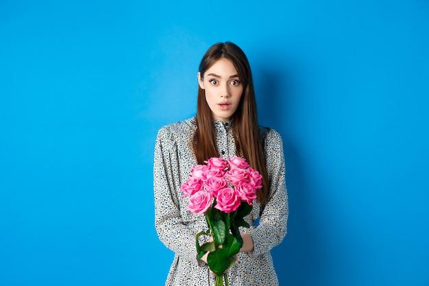 バレンタインデーのコンセプト。青い背景の上に立って、美しい花の花束を受け取り、カメラを信じないで見ている驚いたガールフレンド。
