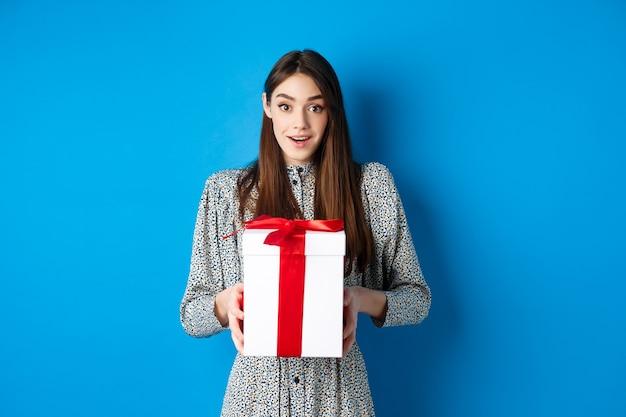 Концепция дня святого валентина. удивленная счастливая девушка получает романтический подарок и благодарно смотрит в камеру, стоя на синем фоне.