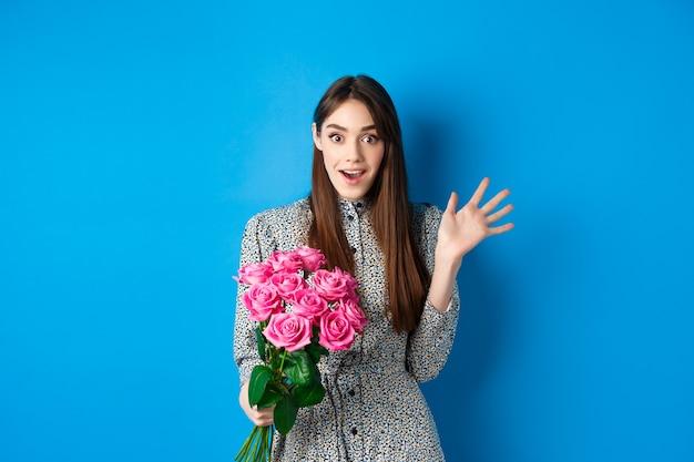 バレンタインデーのコンセプト。恋人から花の花束を持って、青い背景の上に立って、カメラで驚いて幸せそうに見える驚いたかわいい女の子。
