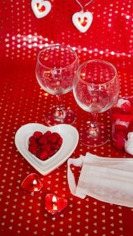 バレンタインデーのコンセプトテーブル。医療用マスクとのロマンチックなディナー。コロナウイルス2021。顔面保護マスクと赤いテーブルセッティング。縦の写真