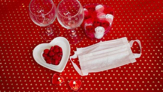 バレンタインデーのコンセプトテーブル。医療用マスクとのロマンチックなディナー。コロナウイルス2021。顔面保護マスクと赤いテーブルセッティング
