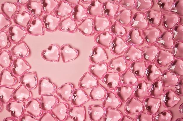 バレンタインデーのコンセプト。ピンクの背景にガラスの透明なハート、ガラスのハートが光る、ガラスの絵の環境で2つの赤いハート。多くの赤いガラスの心。バレンタインデーが大好きです。スペースをコピーします。
