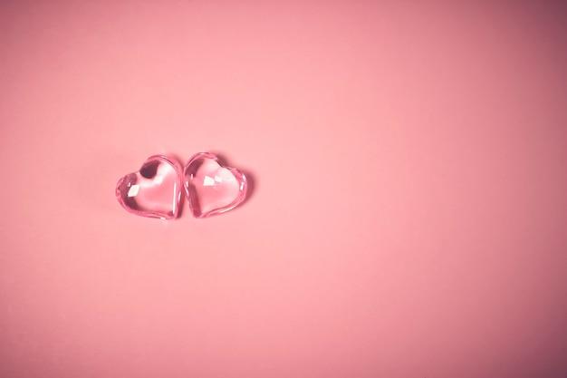 バレンタインデーのコンセプト。ピンクの背景に2つの赤いハート、ガラスのハートが光る、ガラスの絵。バレンタインデーが大好きです。スペースをコピーします。
