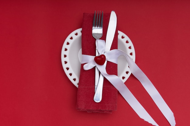 Valentines day concept. white plate in the shape of a heart and cutlery.